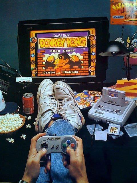 Garoto jogando Donkey Kong do Game Boy no Super Nintendo.